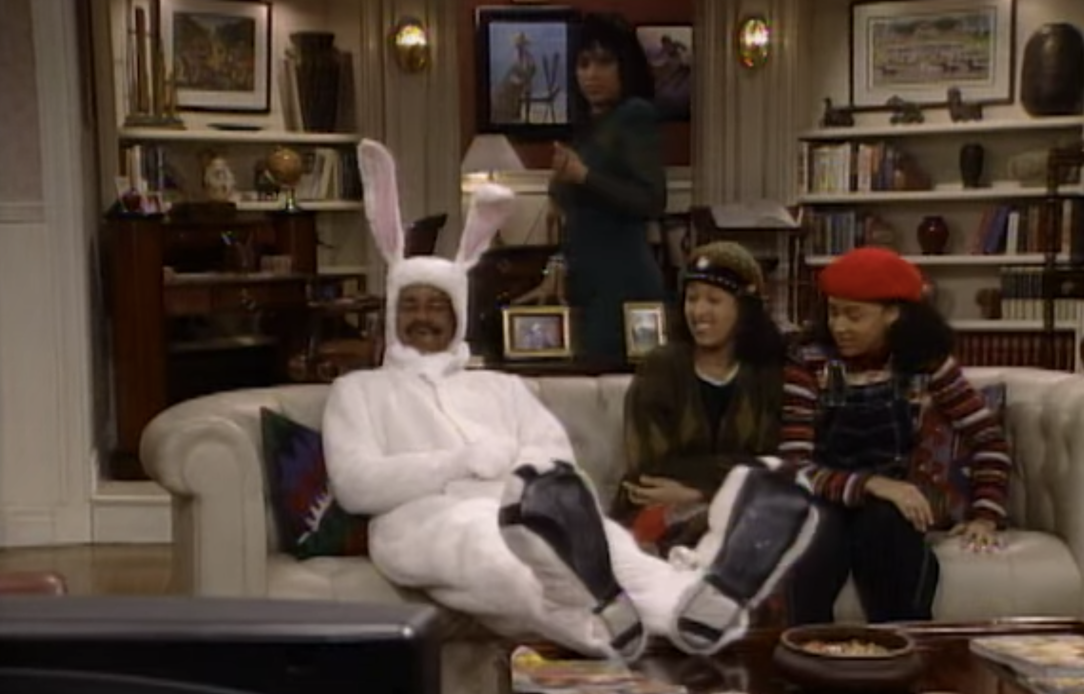 Ray sitting on the couch in a bunny costume next to Tia and Tamera