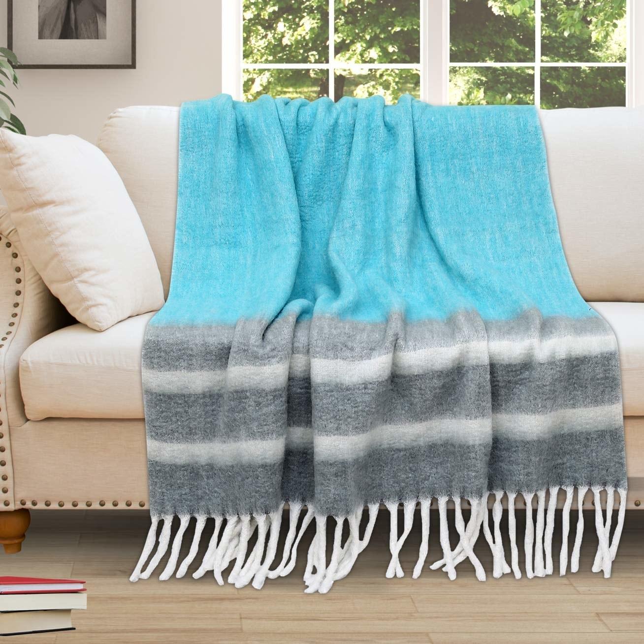 The throw blanket draped on a beige sofa.