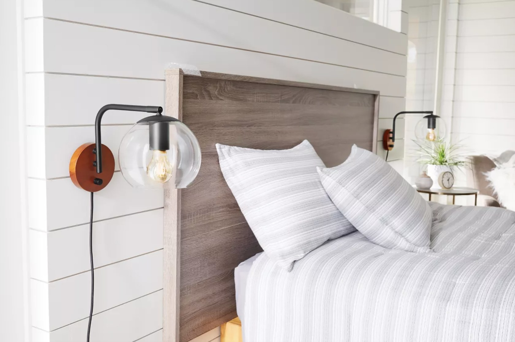 A wall sconce with wooden base, black metal arm, and round glass shade