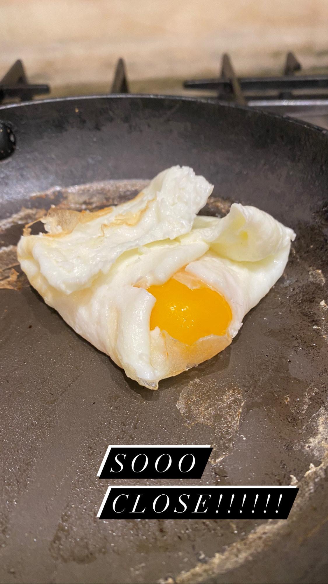 An egg yolk falling out of the egg white envelope.