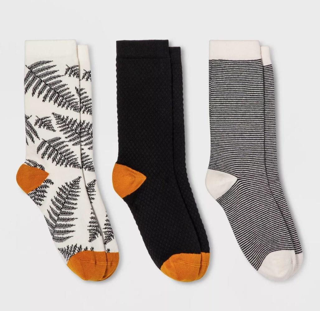 Three pairs of crew socks: white socks with black leaf design and orange detail, black sock with orange detail, black and white stripe sock with white detail