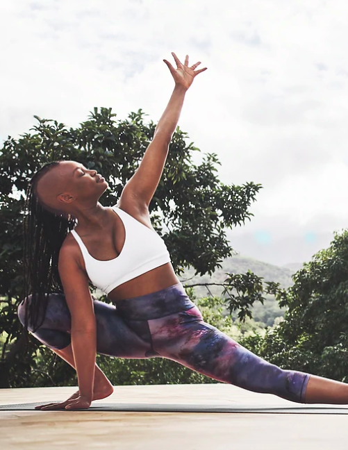 Model wears white strappy back bra with pink, dark, blue, and purple marble-print capris  while stretching on a mat