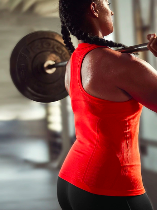 Model wears bright red workout tank while lifting a barbell