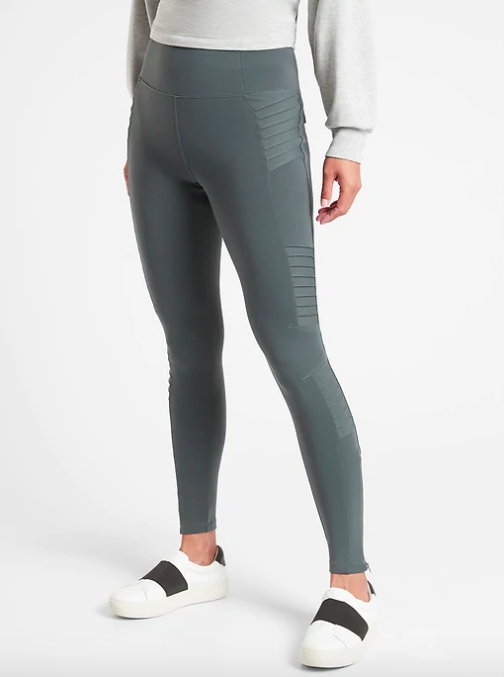 Model wears moto-design gray leggings with white and black slip-on sneakers