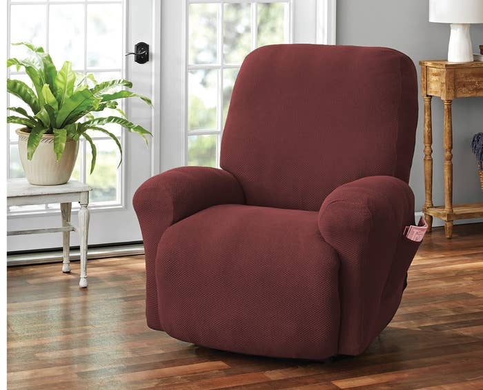 A recliner, covered in the slipcover in maroon, with side pocket