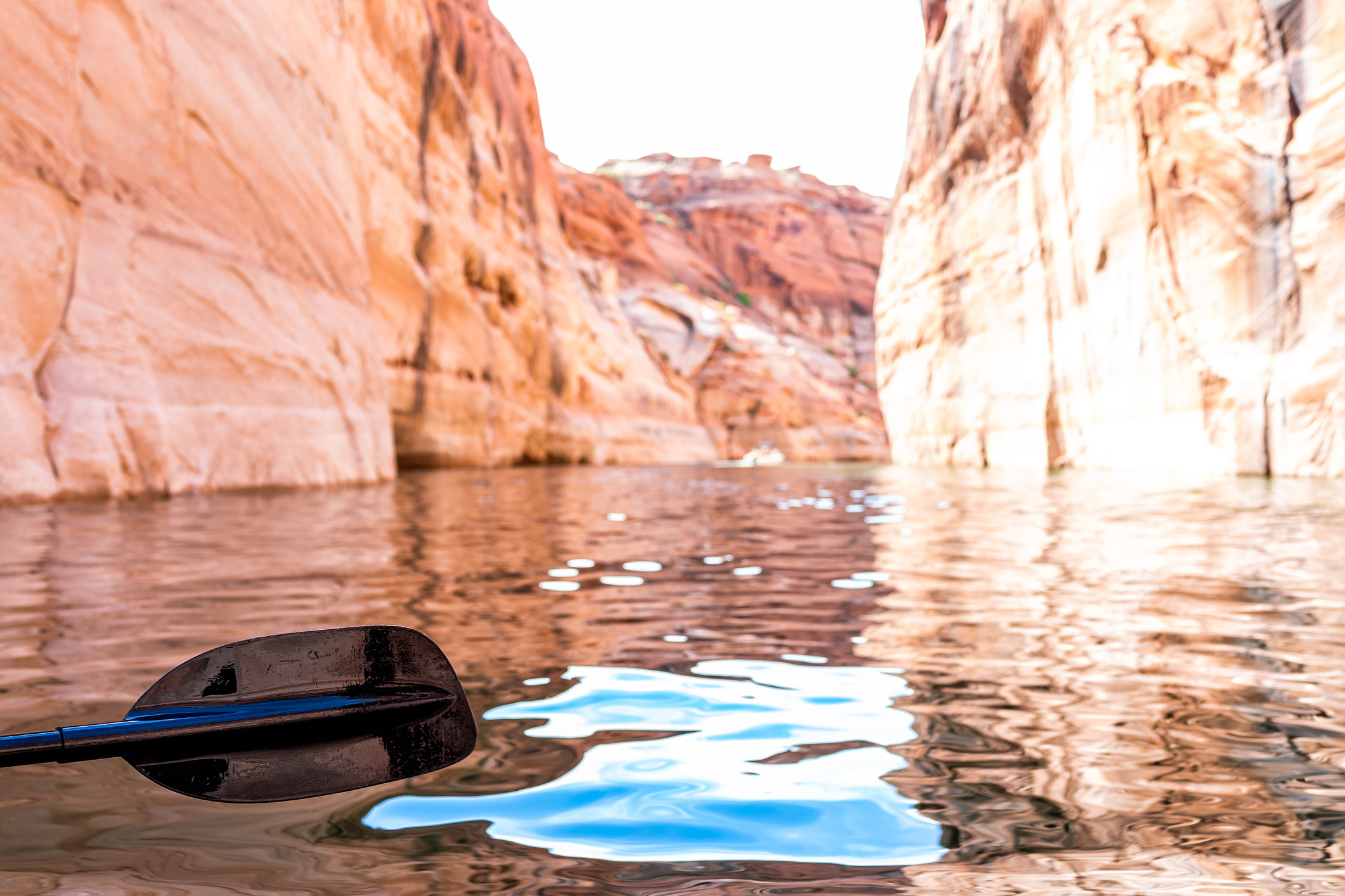 a kayak paddle in the water, a narrow river surrounded by sandstone cliffs