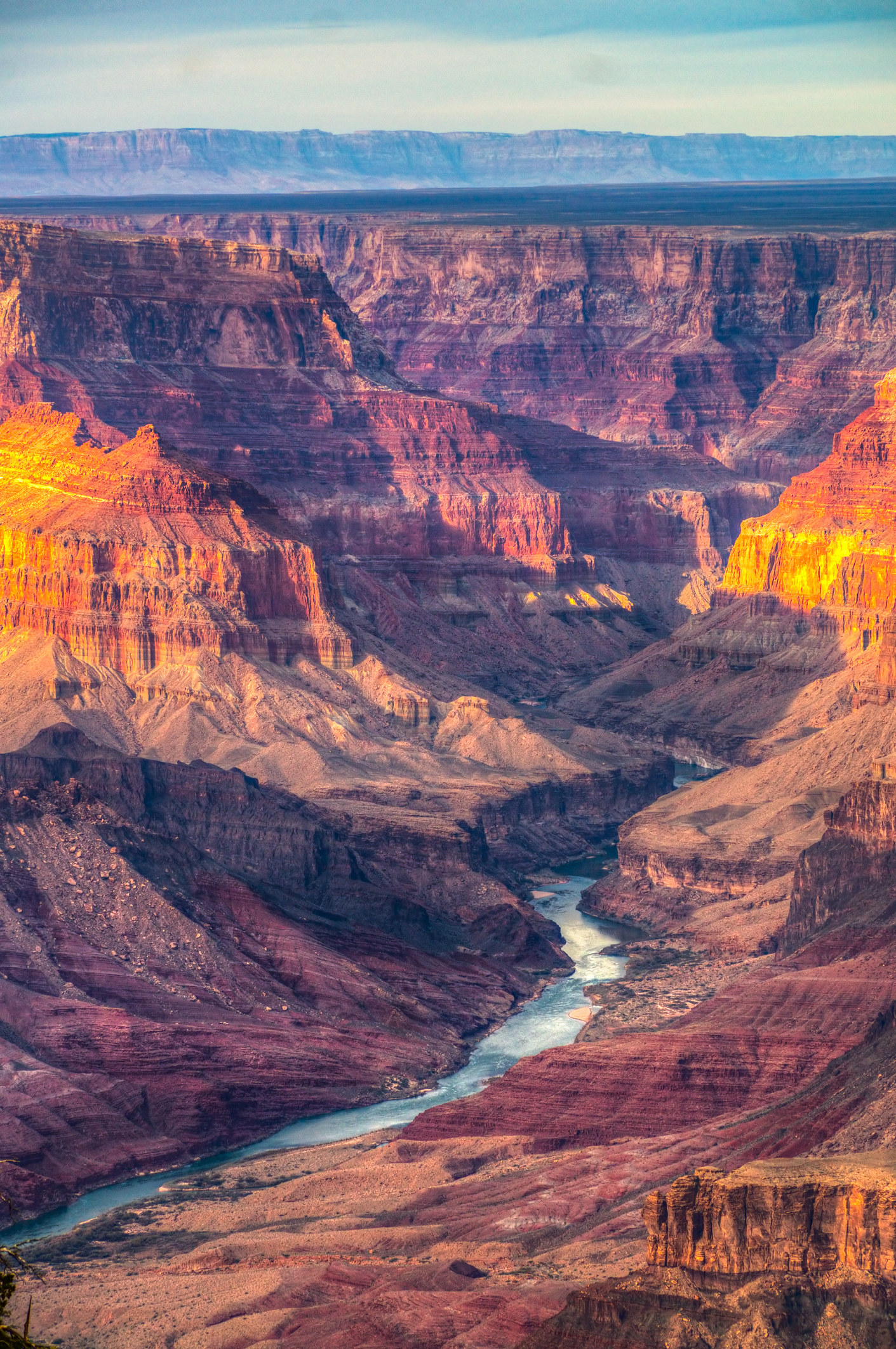 dusk light shines over a giant rocky canyon with a river at the bottom