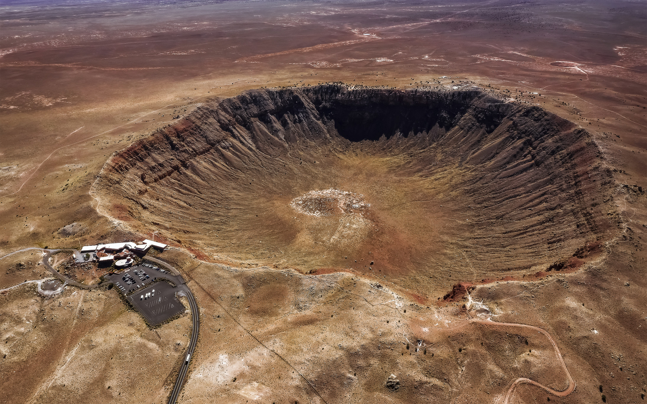 bird's-eye view of a giant crater with rippled edges in the ground
