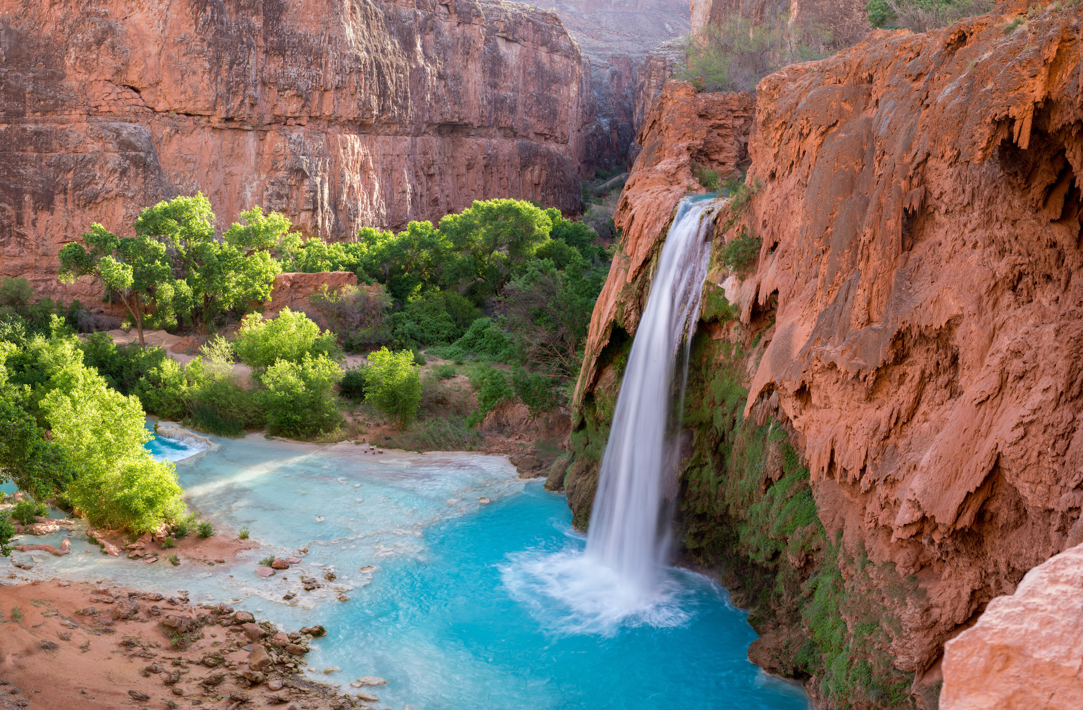 a waterfall flowing over red cliffs into a bright blue pool