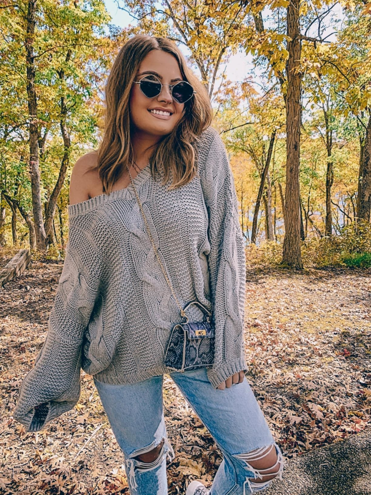Reviewer wearing the sweater off-the-shoulder style in grey