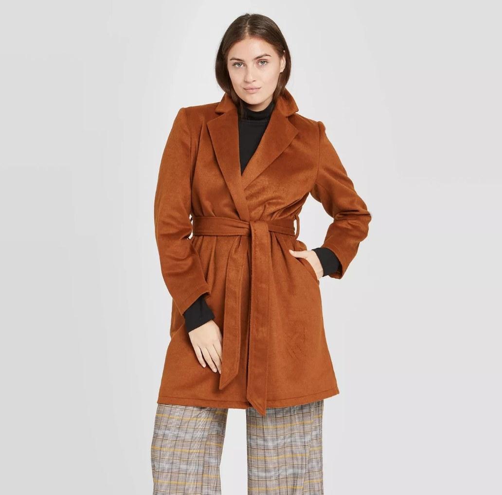 Model wearing copper colored wrap overcoat