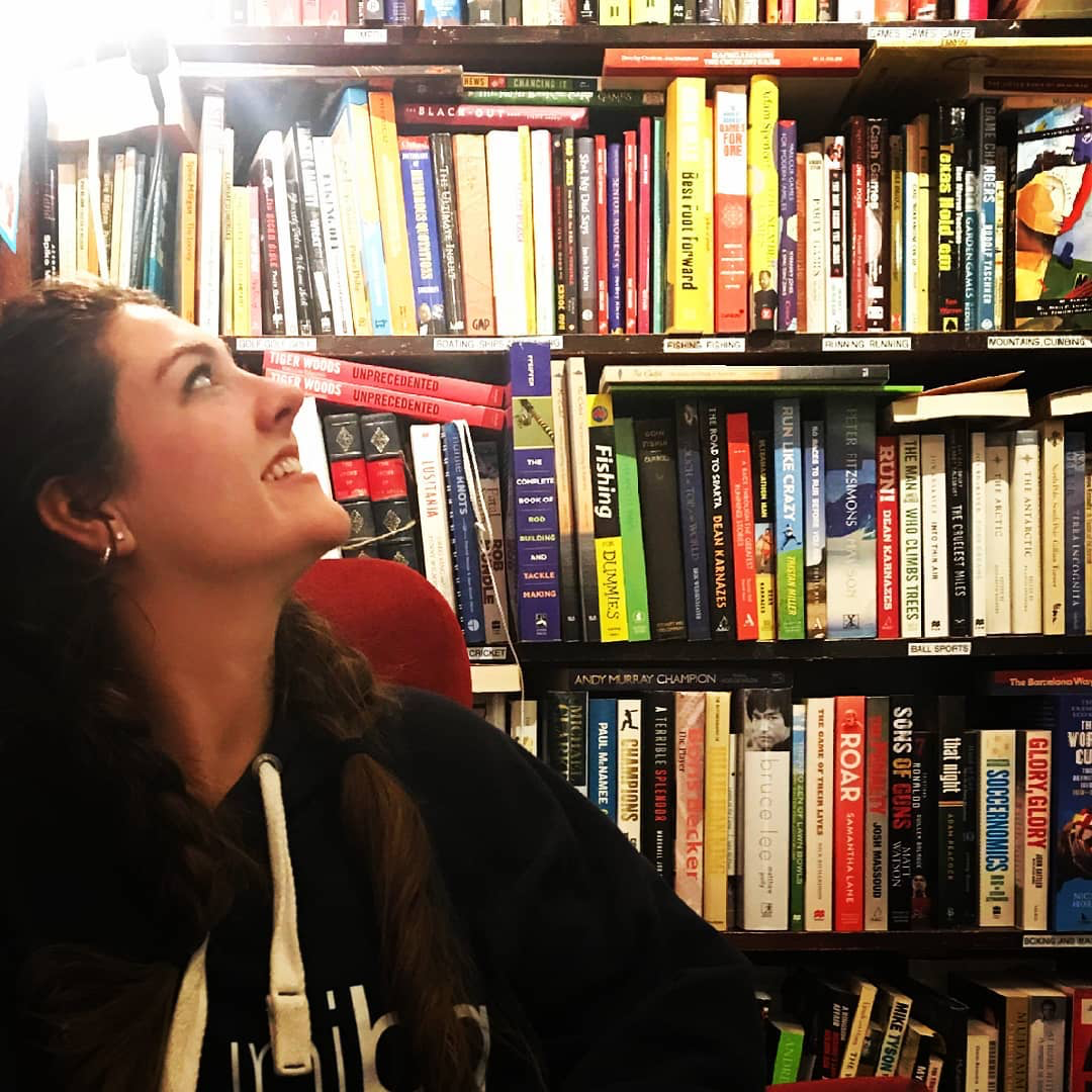 Woman with long dark hair looking up at a huge bookcase behind her