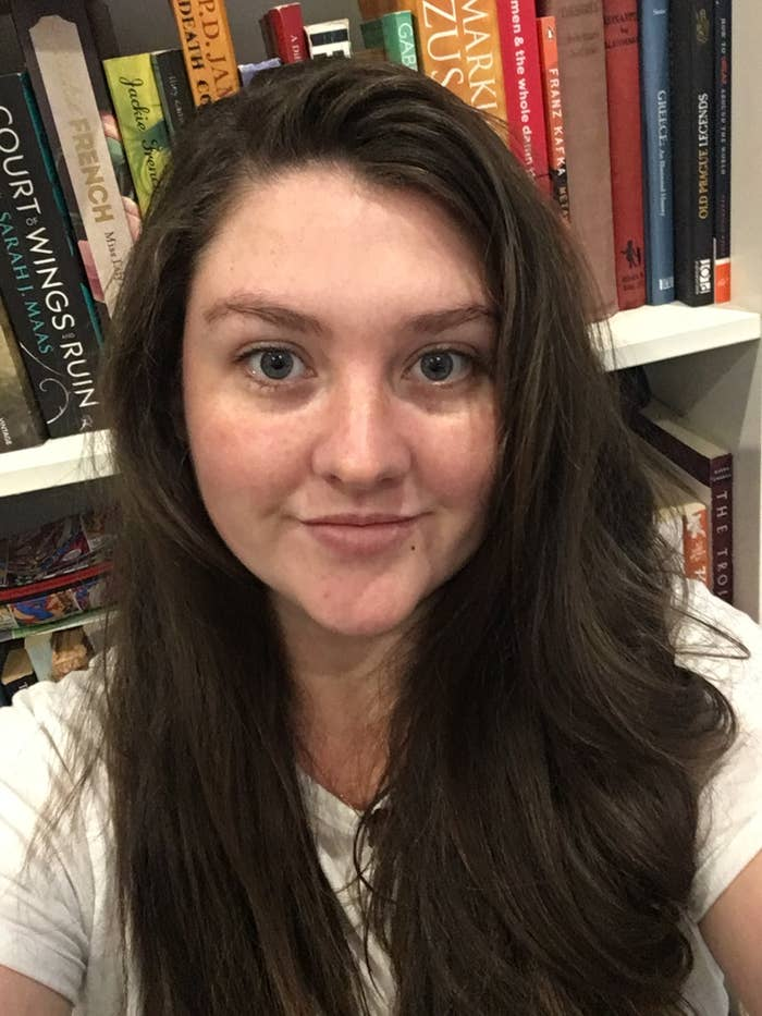 Woman with long dark hair and blue eyes taking selfies in front of a bookcase