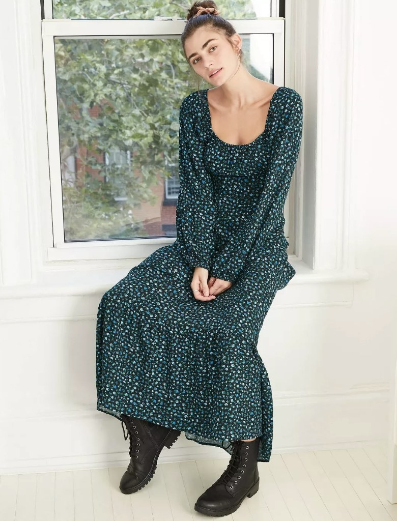 Model wearing deep blue long sleeve/floor length floral dress with black combat boots
