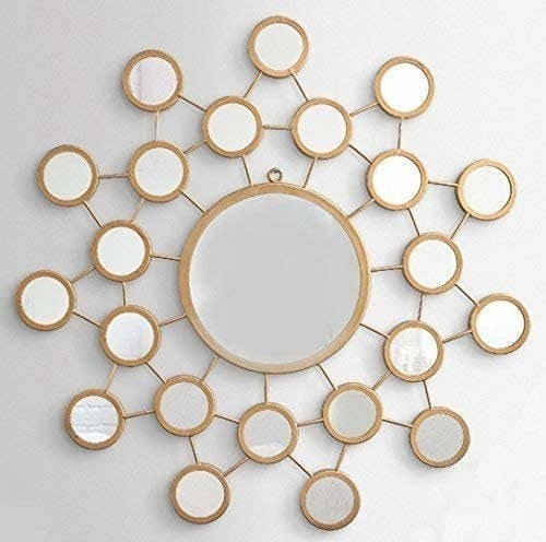 A wall mirror with a large golden-rimmed mirror in the centre and several smaller golden-rimmed mirrors protruding outwards, like the sun.