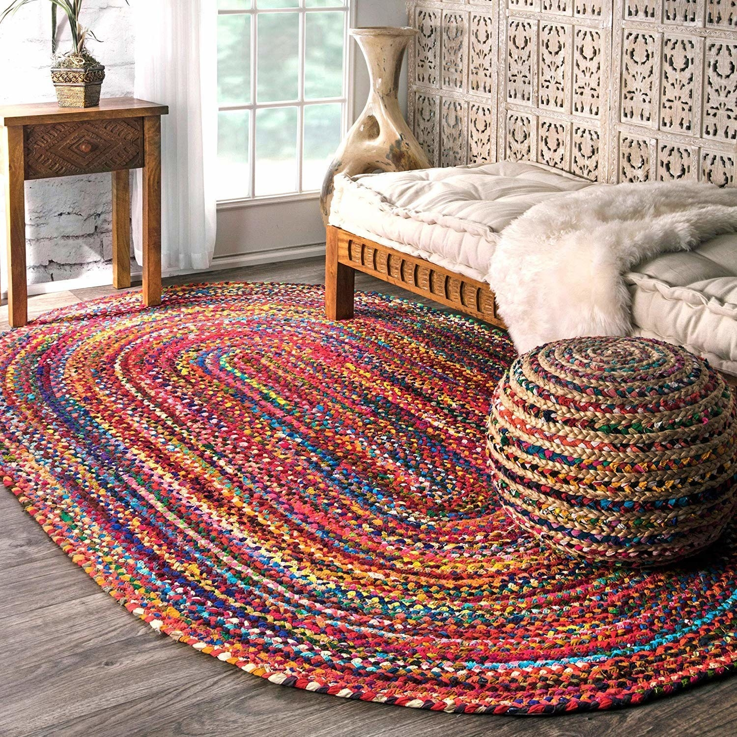 A colourful braided rug pictured in a room.