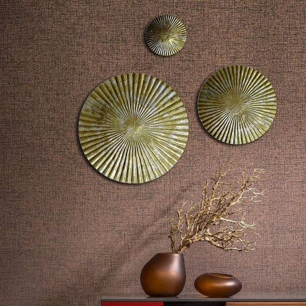 Pleated round metal wall decorations with a chipped, antique golden and silver paint.