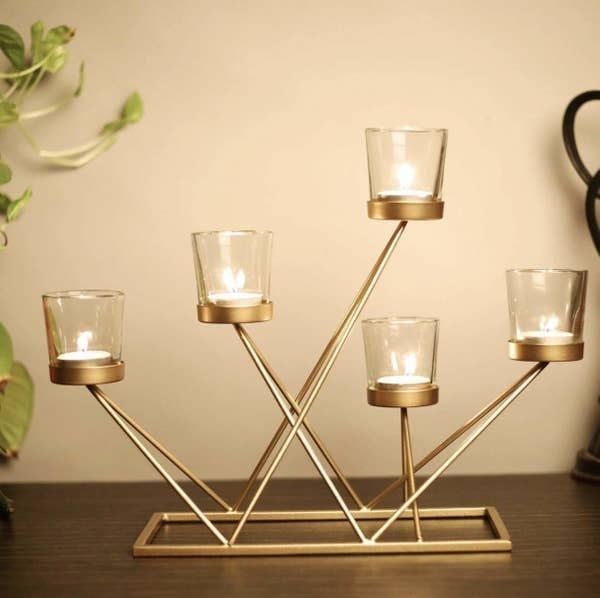 A golden candelabrum with five glass candle holders.