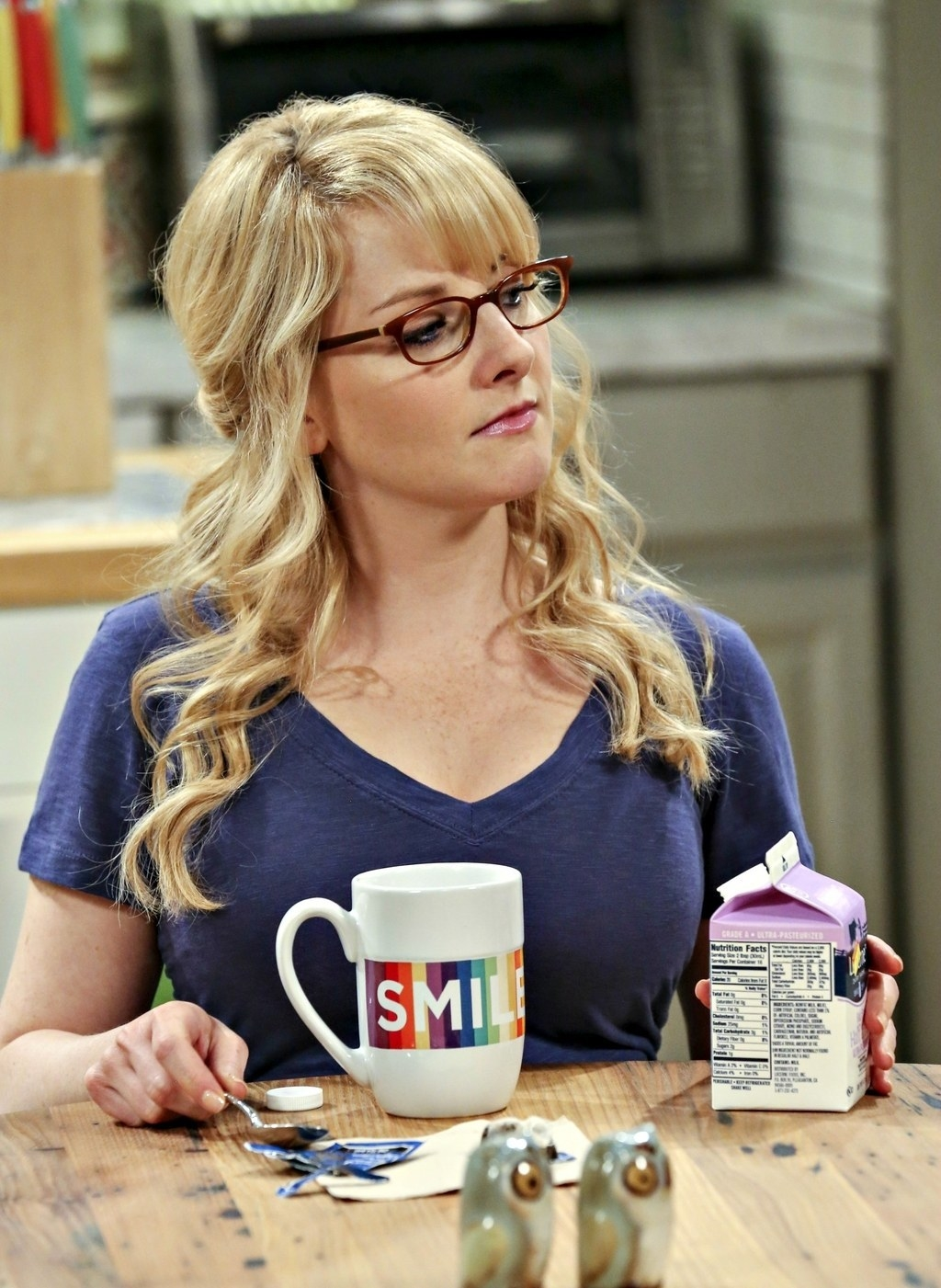 "Brittany holding a carton of milk; she's sitting down at a table and there's a ""Smile"" mug on the desk"