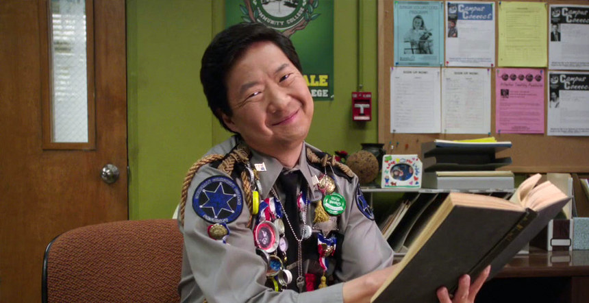 Chang smiling at the camera while holding an open book at his desk