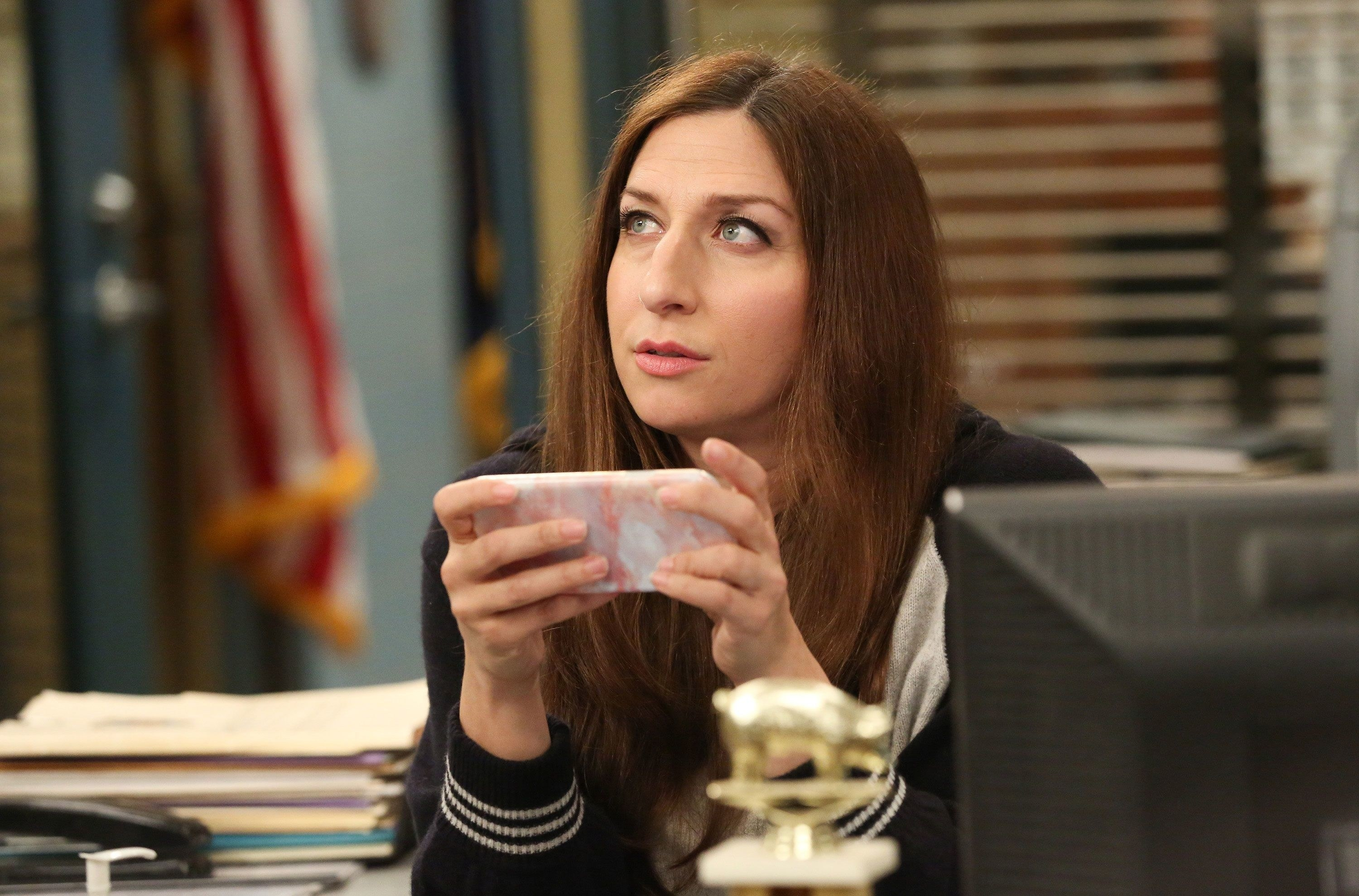 Gina is sitting at her desk while holding her phone to watch something on it; she is looking off into the distance