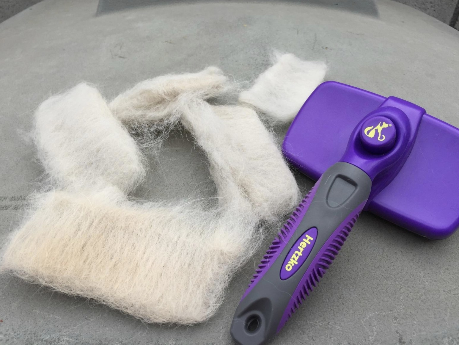 A purple hertzko self-cleaning brush with mounds of fur sitting next to it