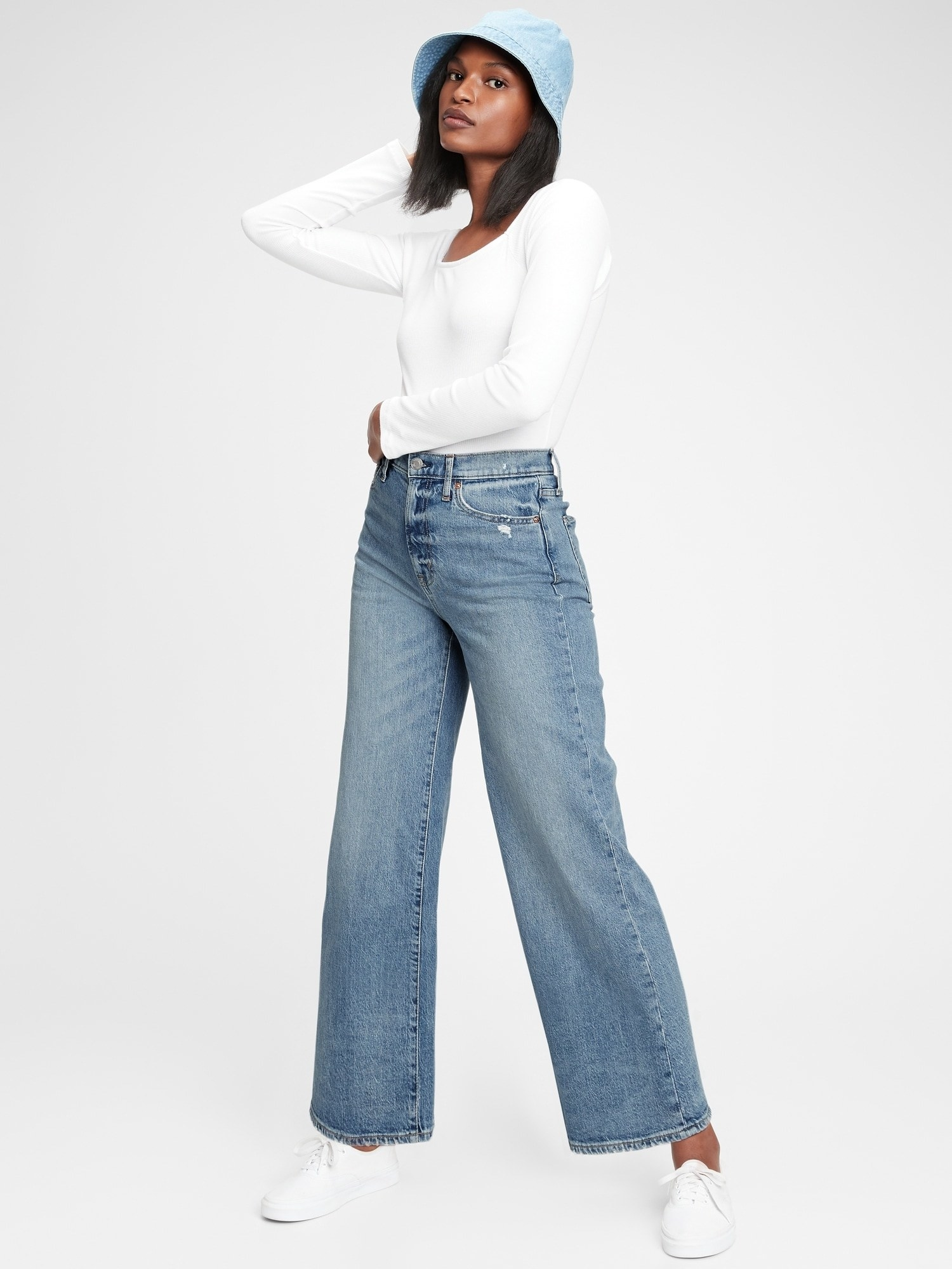 model wearing sky high wide-leg jeans in medium indigo wash with white long-sleeve t-shirt and white sneakers