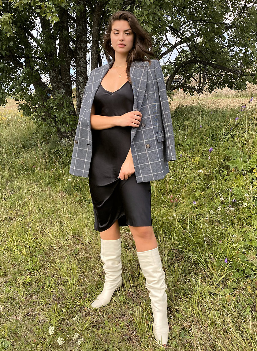 model wearing black slip dress with plaid blazer and white boots