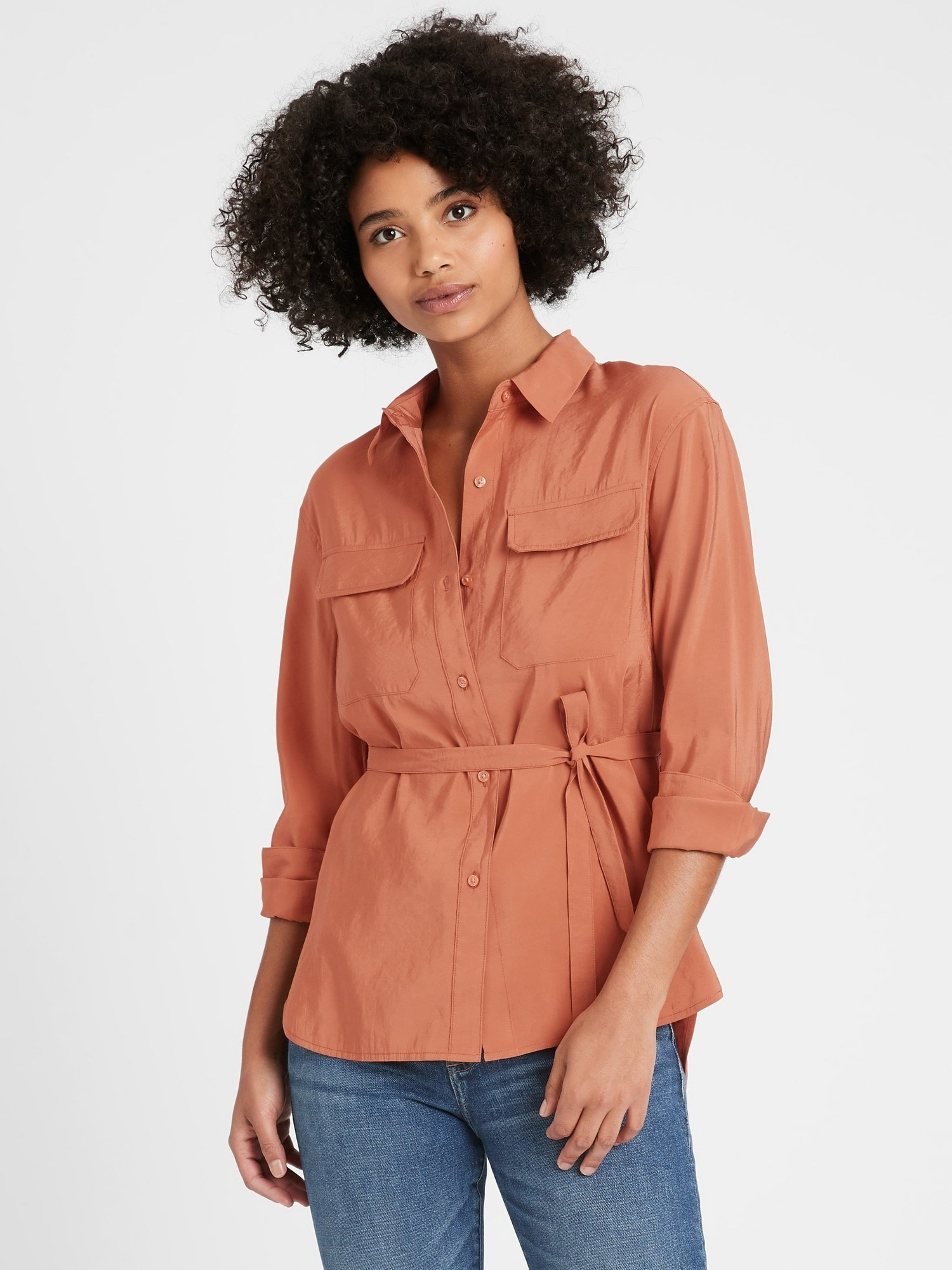 The button-down shirt with pockets on either side of the chest, rolled sleeves, and a tie around the waist