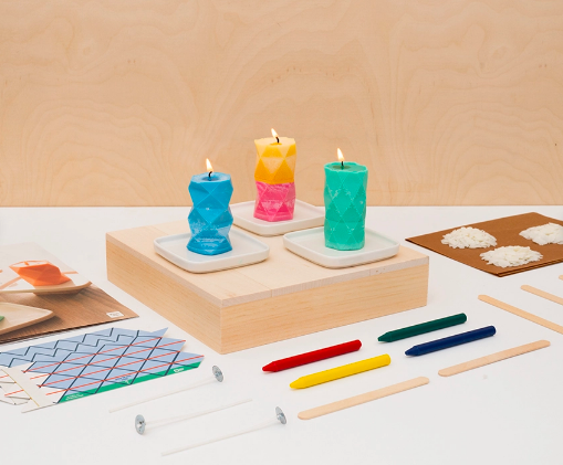 Three geometric standing candles in different colors with tools and ingredients from the kit around them