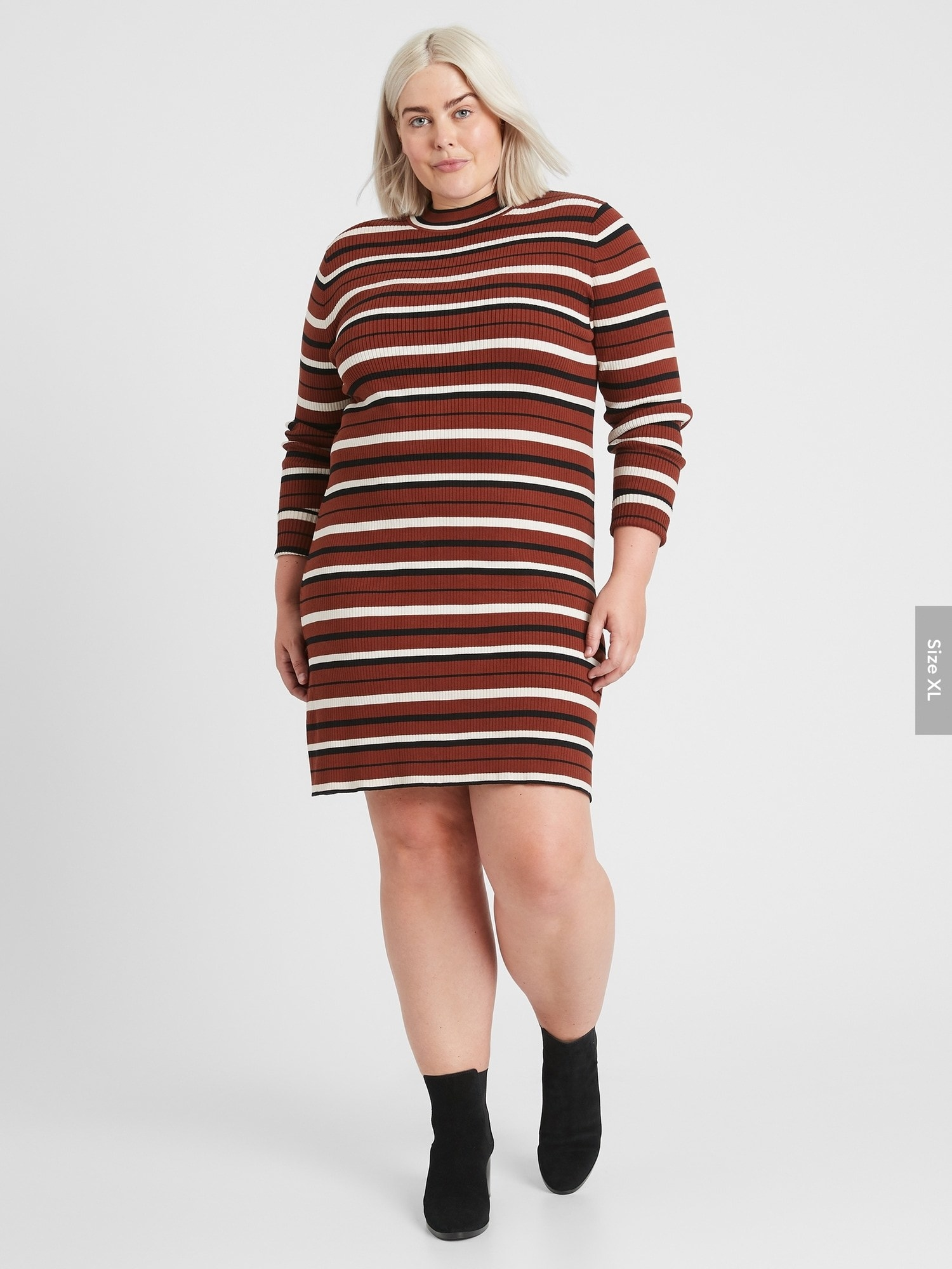 Model wearing the mid-thigh length long-sleeved bodycon dress with orange, black, and white horizontal stripes