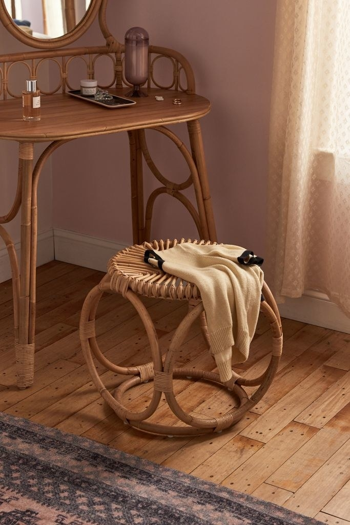 A circular wooden wicker style stool with a circular geometric style