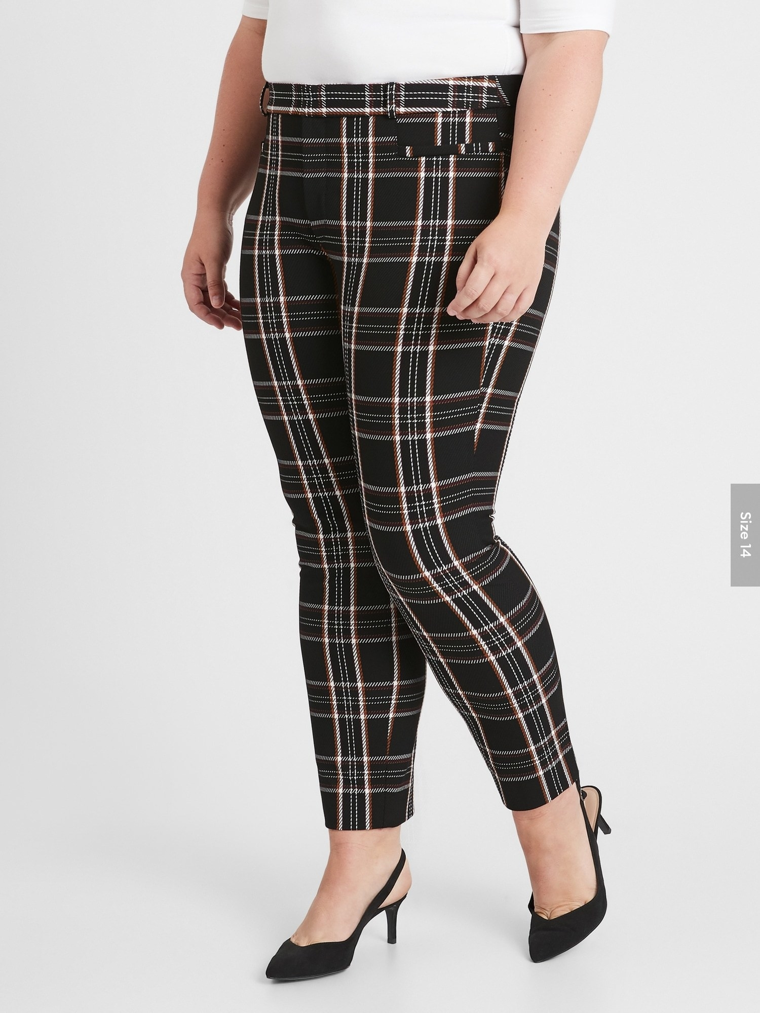 Model wearing the ankle-length pants in black with a white and red plaid pattern