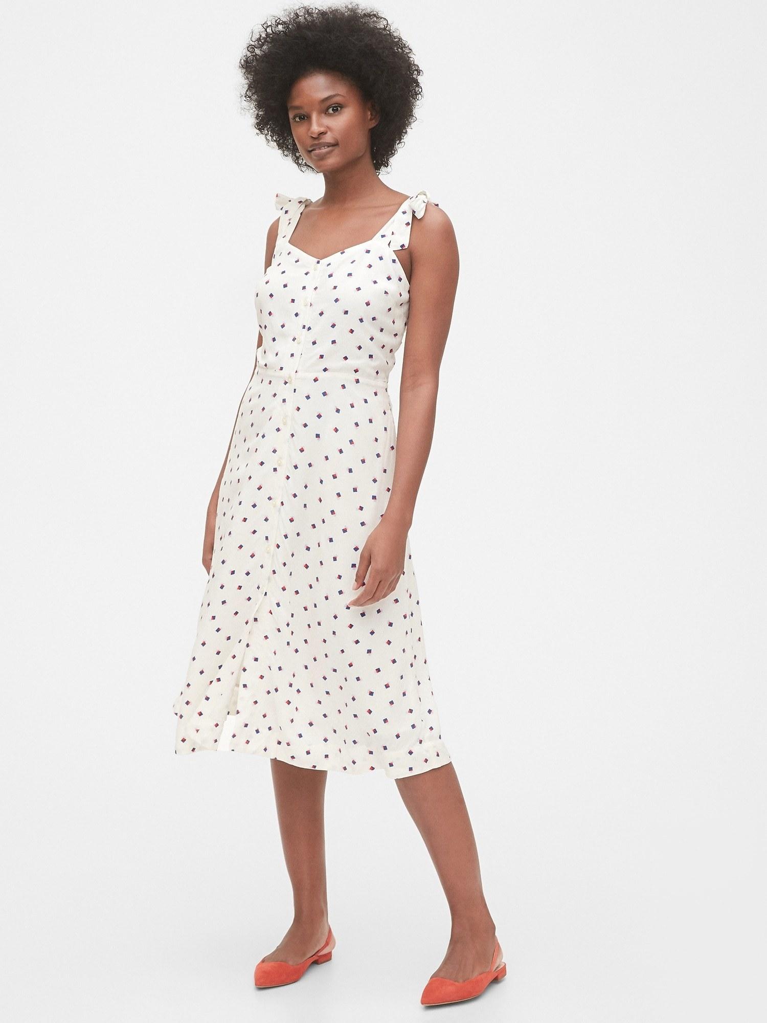 model wearing tie-strap cami midi dress in white print