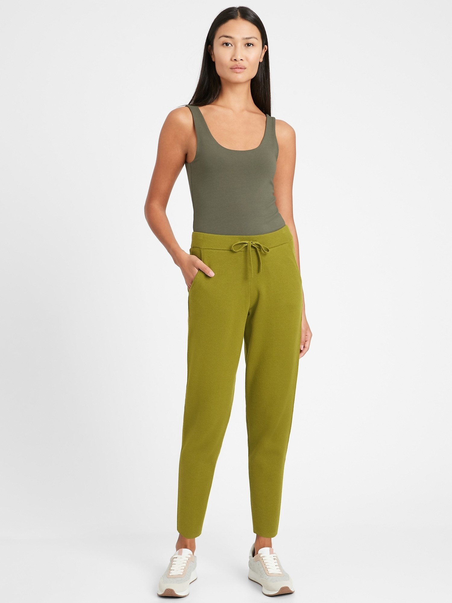 Model wearing the ankle-length joggers with pockets and a tie at the waist in bright green