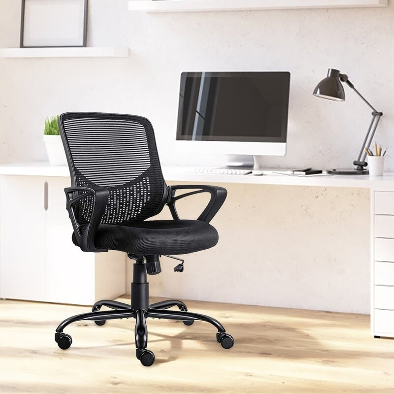 The black mesh-back rolling desk chair