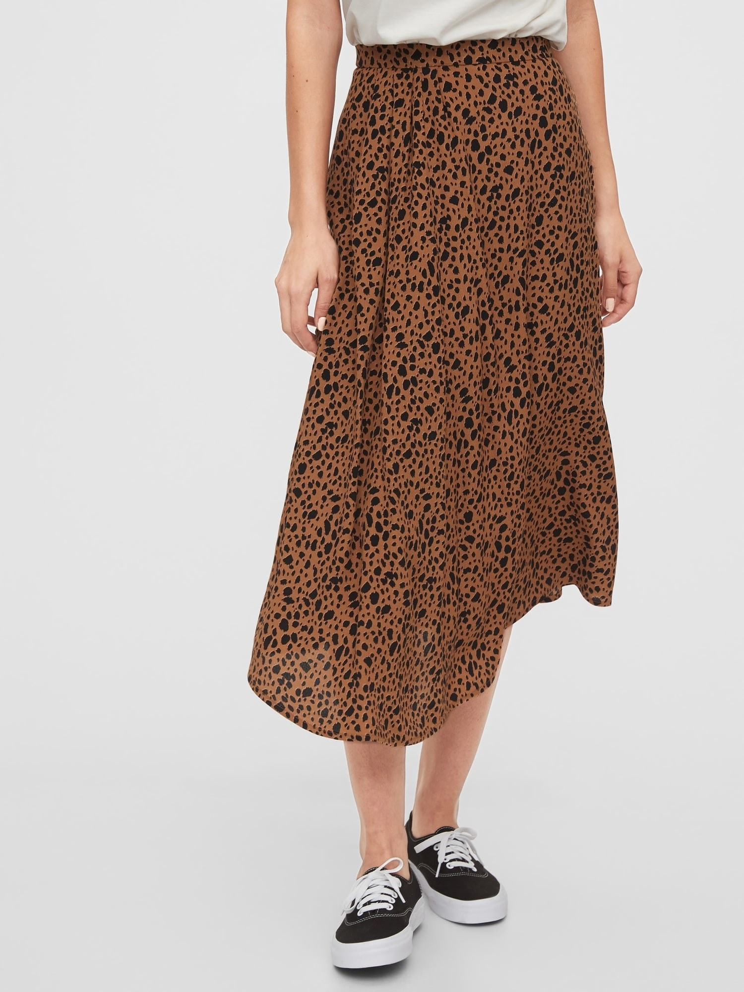 model wearing midi skirt in leopard print with black sneakers
