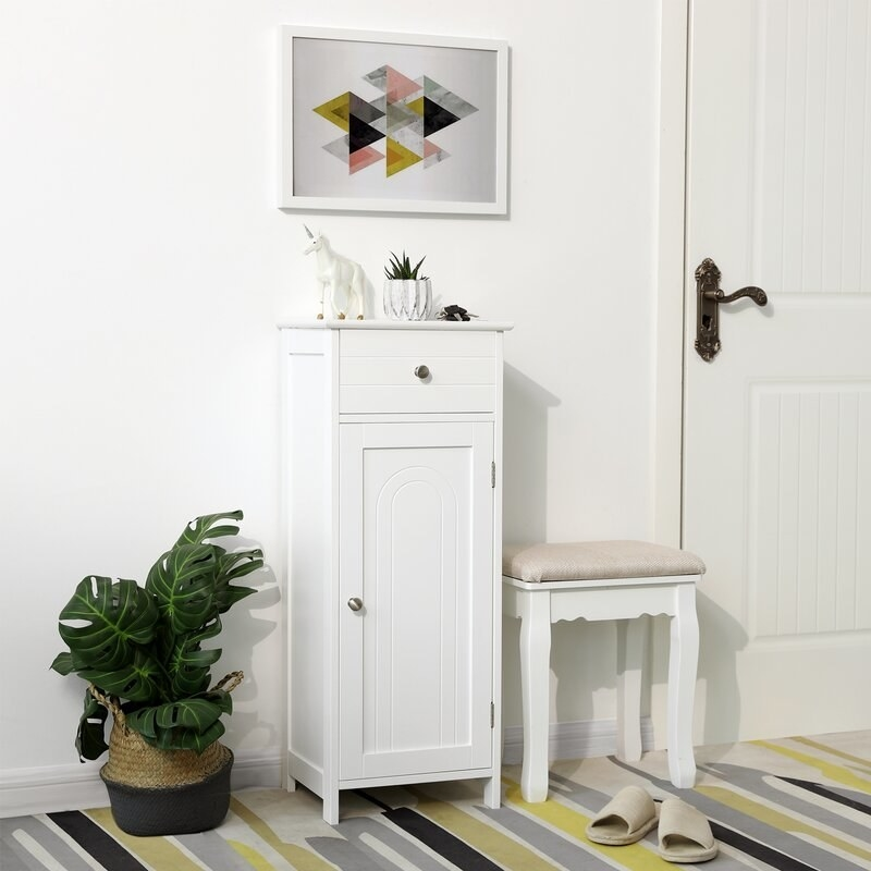 The slim cabinet in white with a tall front-facing door and a drawer on top