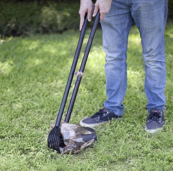 Pet owner uses pooper scooper in yard