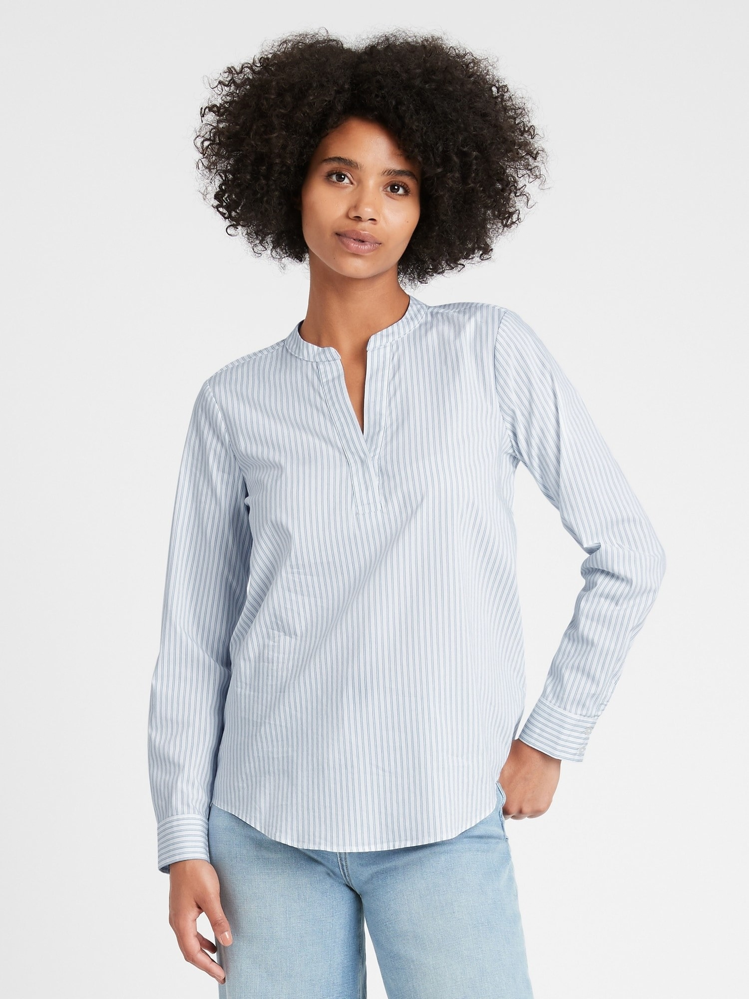 Model wearing the notch-neck rounded-hem shirt with black and white vertical stripes
