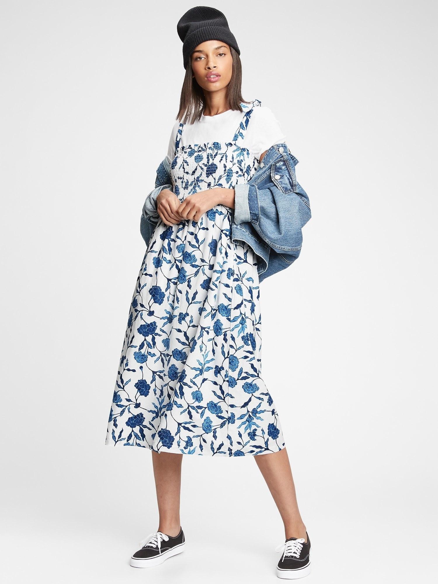 model wearing smocked tie strap midi dress in blue floral
