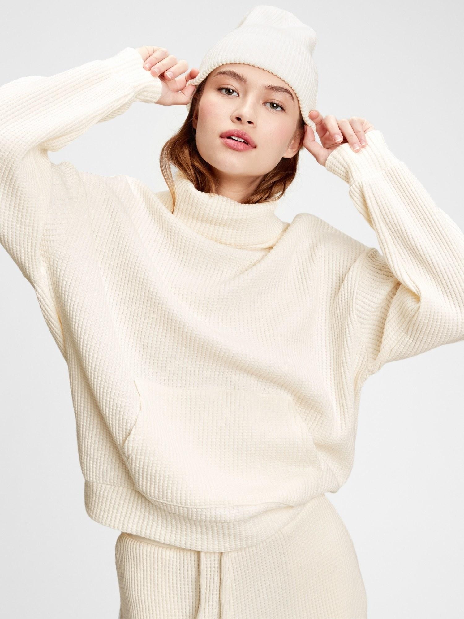 model wearing waffle-knit turtleneck pocket sweatshirt in antique white