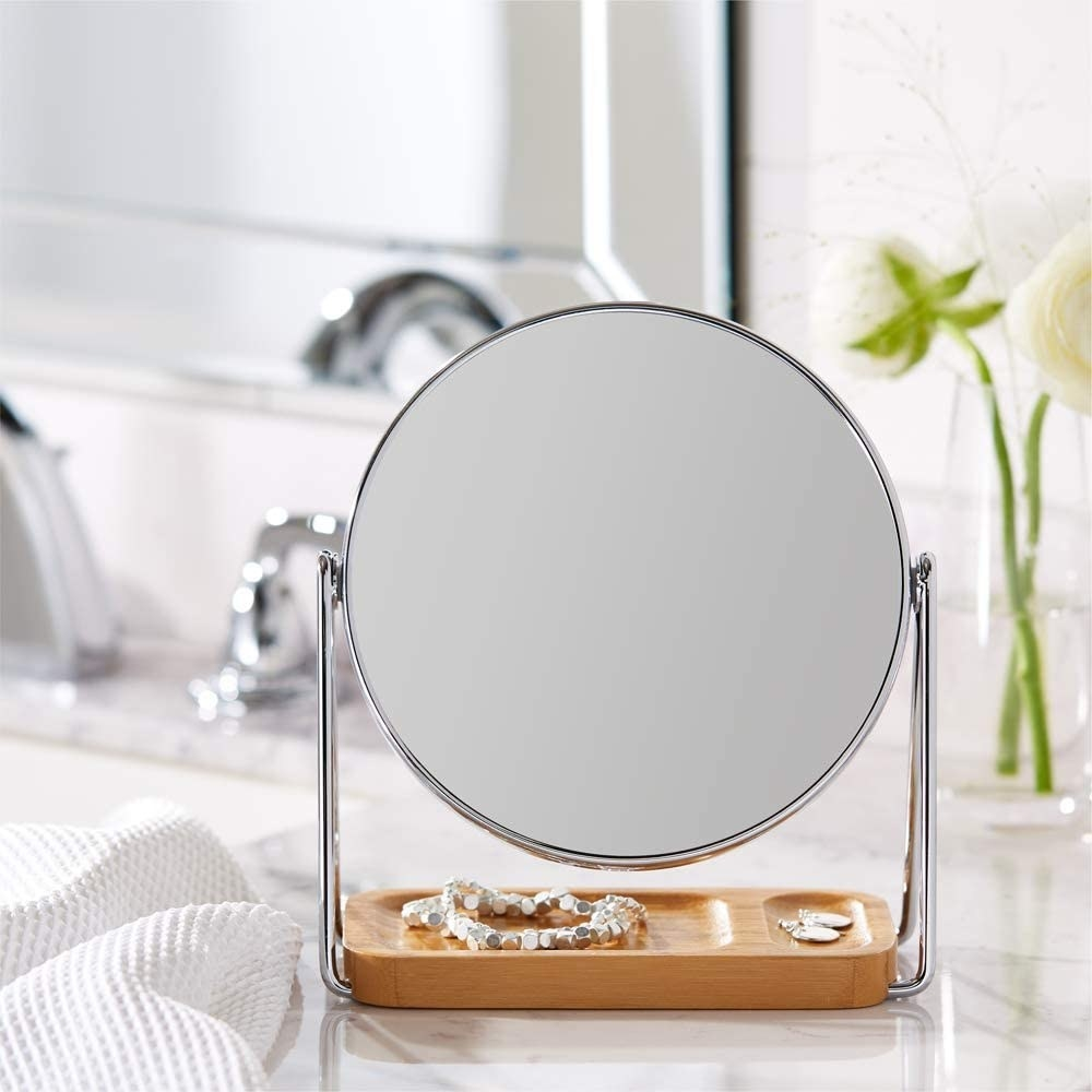 A close up of the circular mirror with a bamboo tray in a bathroom