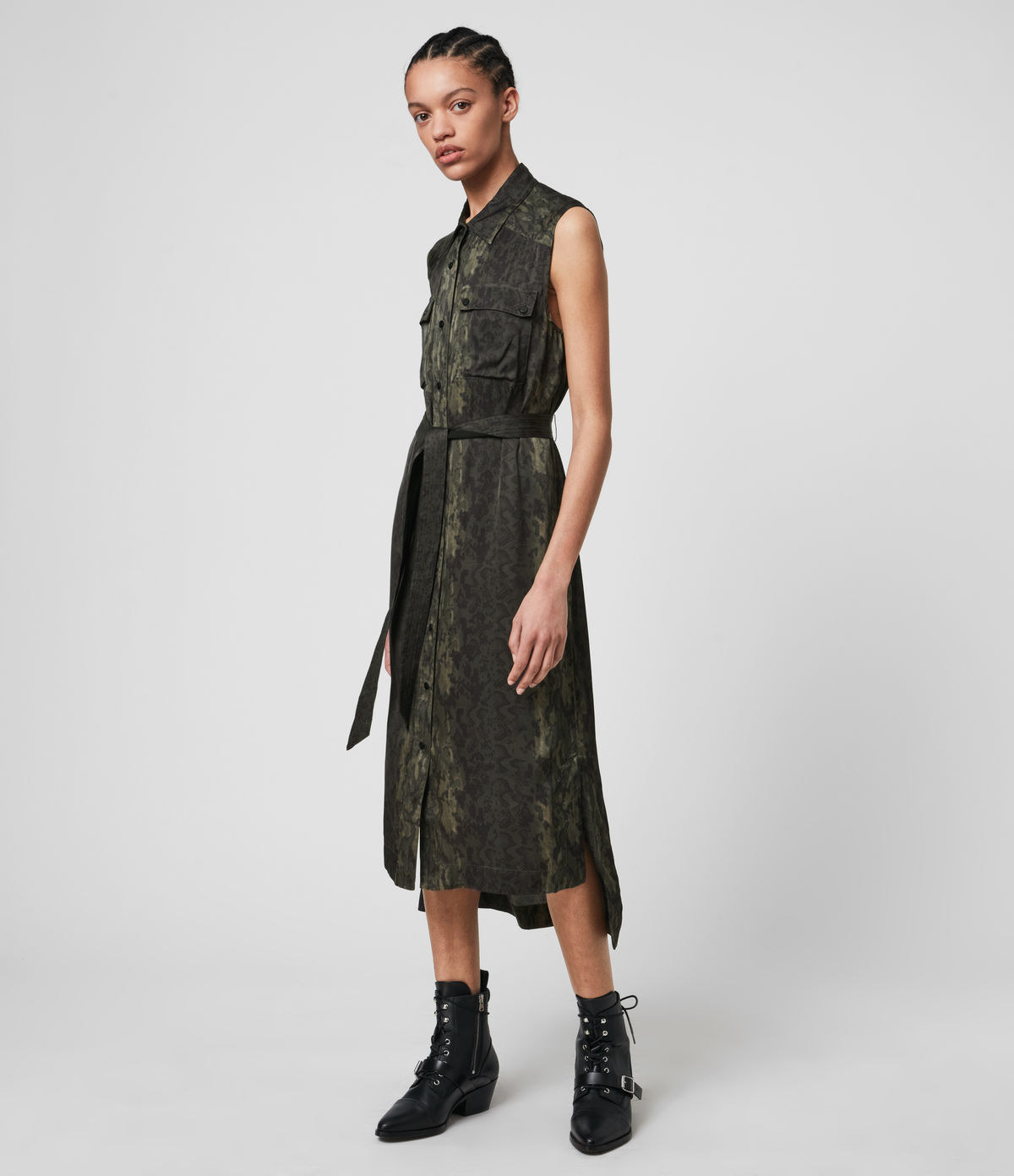 model wearing sleeveless button up shirt dress in dark green snakeprint