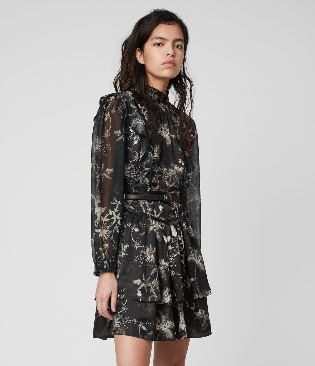model wearing long sleeve mini dress with high neck, sheer sleeves, two tiers on skirt in black floral print