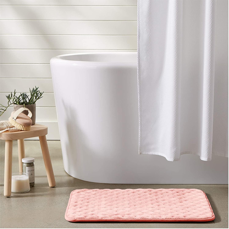 The textured bath mat next to a free-standing mat