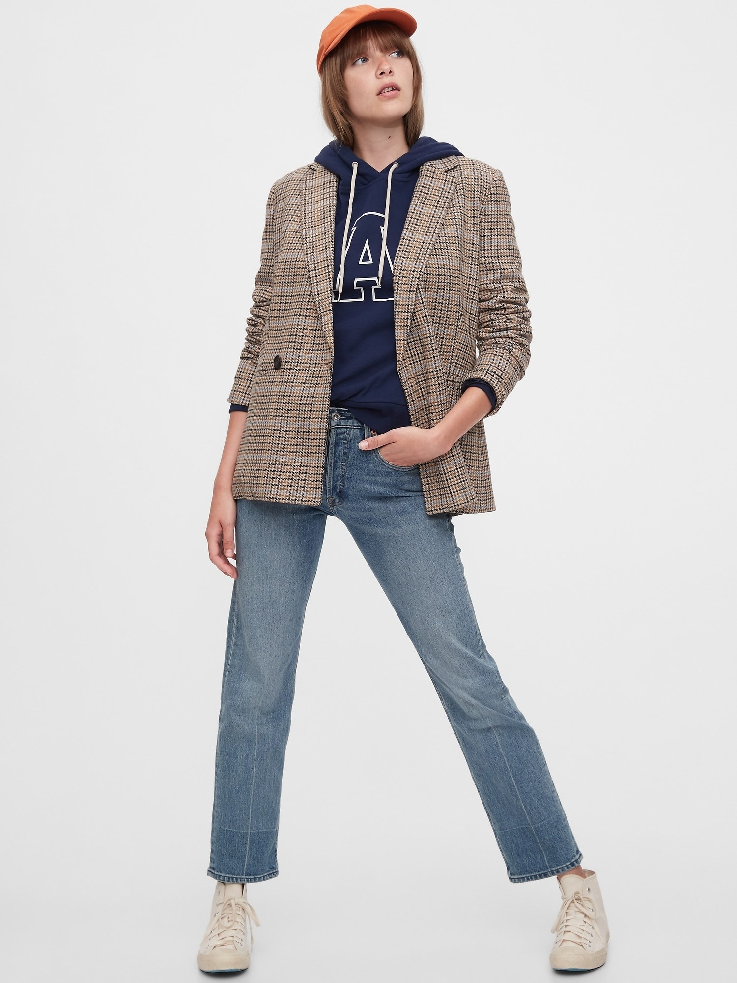 model wearing double-breasted blazer in brown plaid with jeans and a hoodie