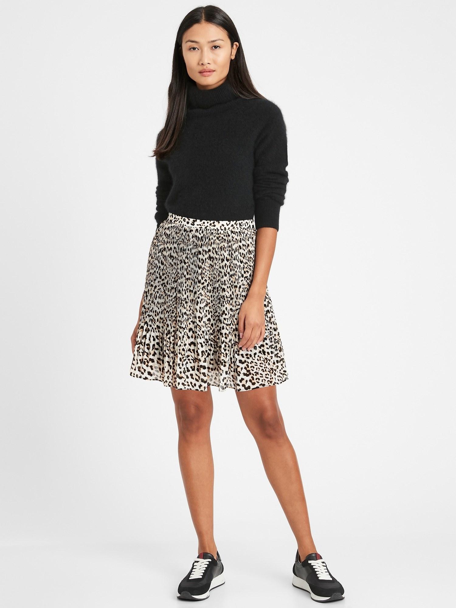 Model wearing the knee-length pleated skirt in leopard print