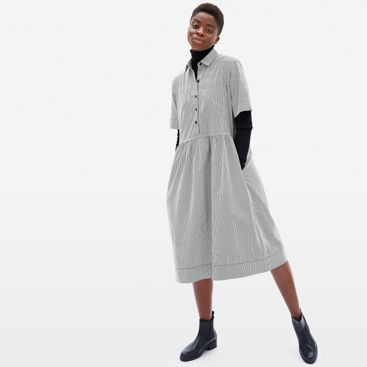 model wearing knee length shirt dress with pockets