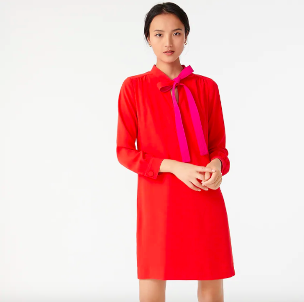 model wearing red shift dress with bow at the neck